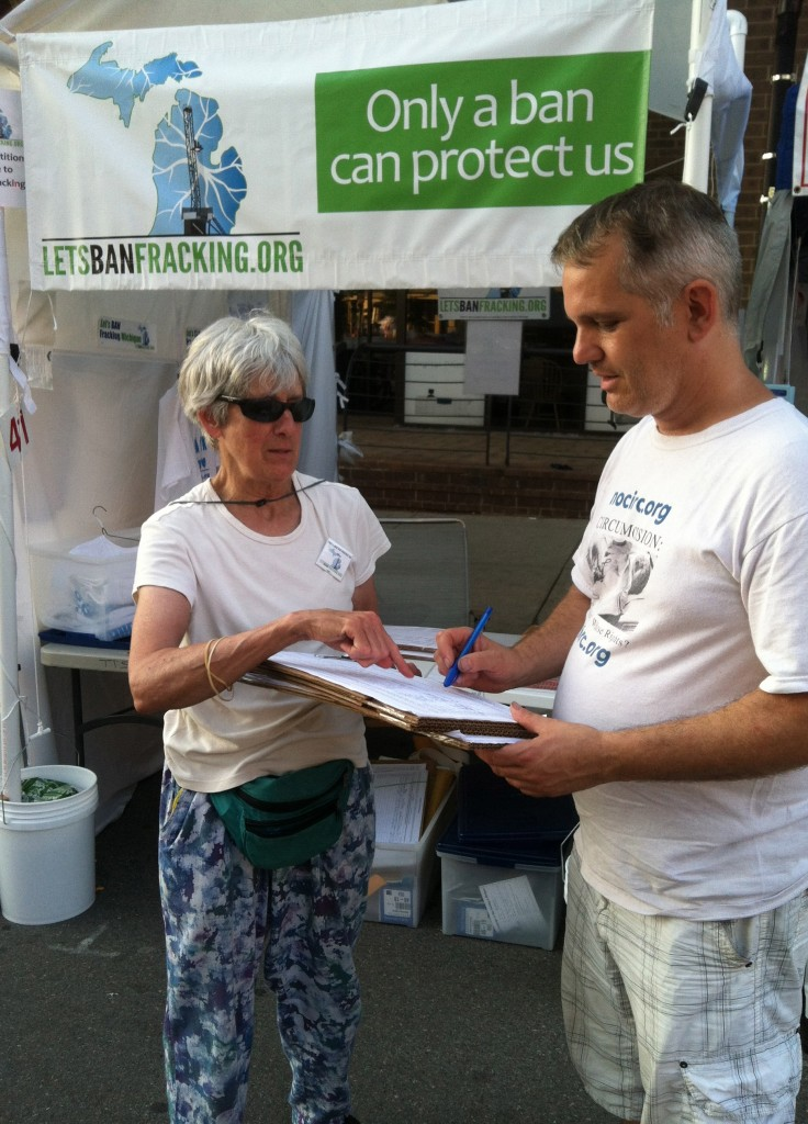 The Committee to Ban Fracking in Michigan is one of the two prominent groups seeking a ban on fracking, by doing a highly-visible ballot initiative statewide. The U of M didn't really notice it. Washtenaw county coordinator Nancy Witter collects signatures at a booth at the Ann Arbor Art Fairs in July 2013. Photo by LuAnne Kozma.
